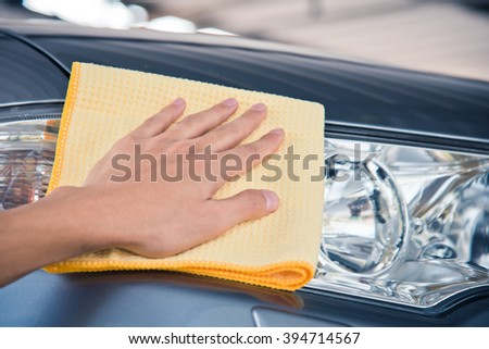 Hand with man cleaning car with microfiber yellow cloth.