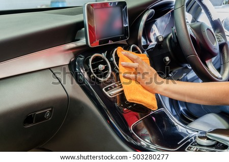 Hand with orange microfiber cloth cleaning interior car.