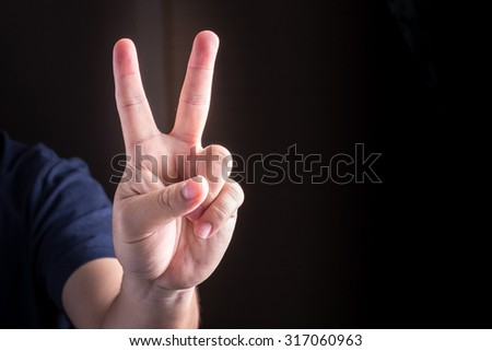 Hand with two fingers up. sigh of peace or victory. Also the sign for the letter V in sign language. studio lights