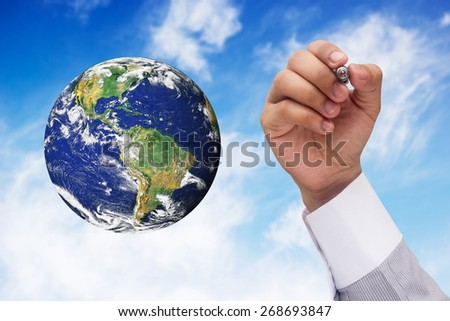 hand writing earth on blue sky backgrounds.Elements of this image furnished by NASA