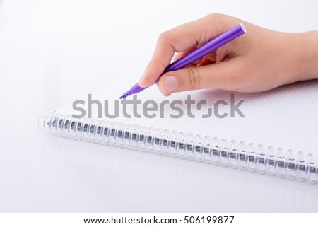 Hand writing on a Notebook with a pen on a white background