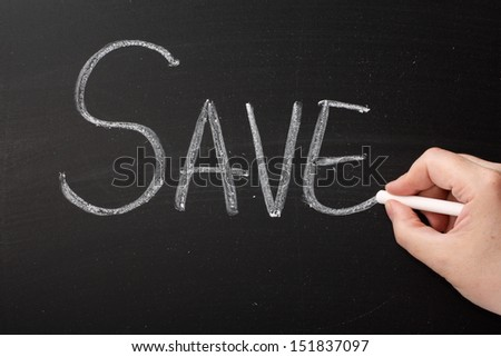 Hand writing the word Save on a blackboard. Savings are made through the purchase of goods and services at a bargain or sale price but also applies to investment and banking and saving energy