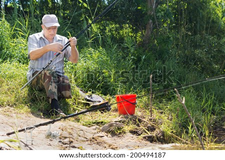 Handicapped man with one leg enjoying a days angling sitting on a grassy bank above a lake or river checking the floats on his line before casting into the water