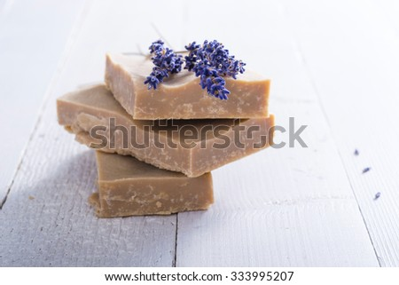 handmade soaps and dried lavender flowers on white wood table background