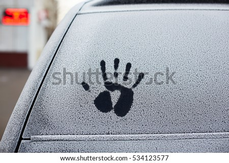 Handprint on the snowy windshield of a car