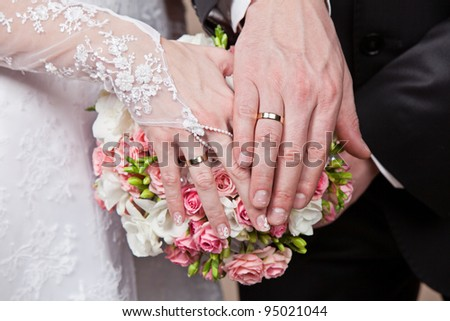Hands and rings on a beautiful wedding bouquet