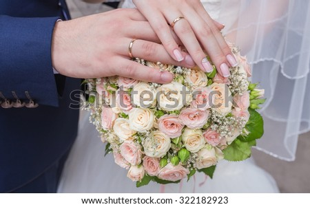 Hands and rings on Beautiful  wedding bouquet