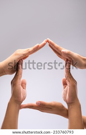 Hands forming shape of a house, isolated on gray