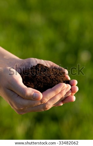 Hands holding soil against a green background. Shallow depth of field. Focus is on the soil