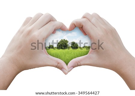 hands in the shape of heart with grass field background