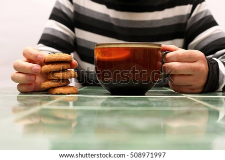 hands of a man with a cup of tea and biscuits