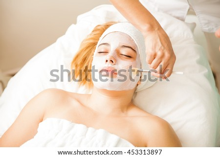 Hands of a therapist doing a facial treatment with a cream mask for a young woman at a spa