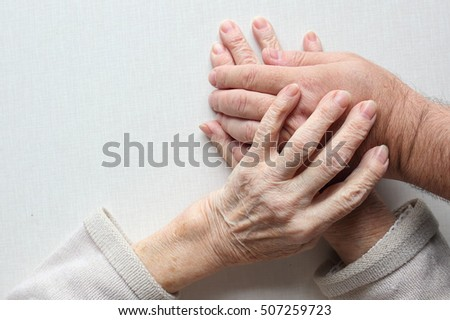 Hands of an old woman holding the hand of a man (son,grandson,doctor,helper). Lonliness, help and patronage concept
