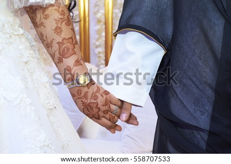 Hands of Arabic bride and groom
