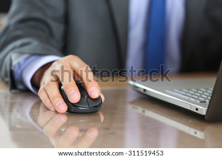 Hands of businessman in suit holding computer wireless mouse working with notebook pc. Working with computer, internet surfing, entertainment or business concept