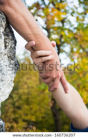 Hands of climber on brink of rock needing the help.