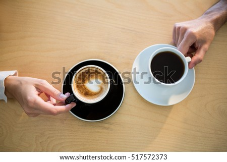 Hands of couple holding cup of coffee in cafeteria