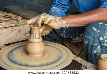 Hands of making clay pot on the pottery wheel.  Ban Tha Hai in Ubonratchathani, Thailand ,select focus, close-up.