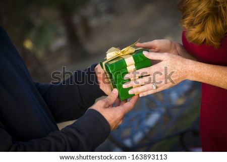 Hands of Man and Woman Exchanging a Wrapped Christmas Gift.