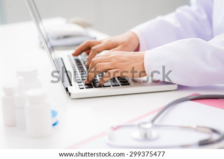 Hands of medical worker using laptop at work