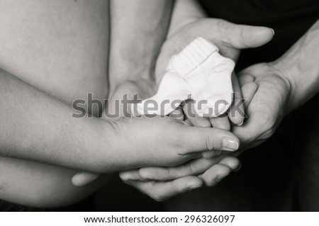 Hands of men and women on pregnant belly with baby socks