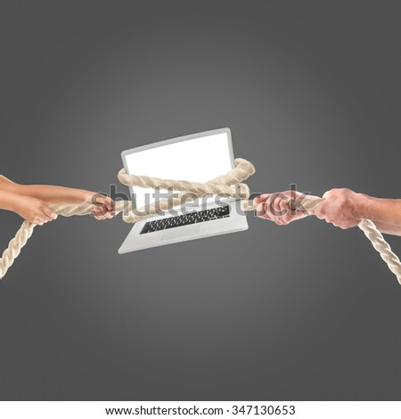 Hands of people pulling the laptop rope on black background. Competition concept