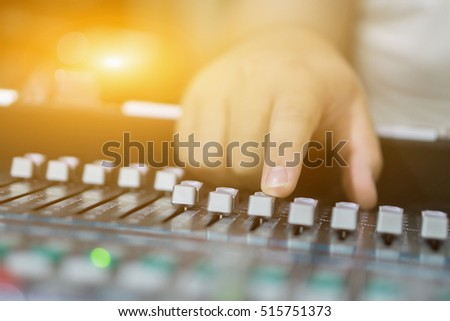hands of sound engineer working on recording studio mixer,Expert adjusting the volume ,vintage color