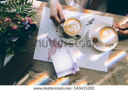 Hands of the bride and groom for a cup of coffee. Wedding bouquet on the table. Marriage concept.