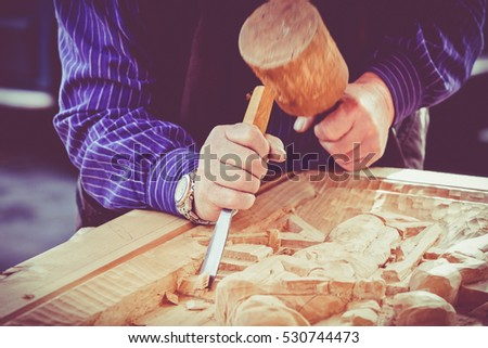 hands of the craftsman carve a bas-relief with a gouge. Craftsman hands working. Work Of Artist