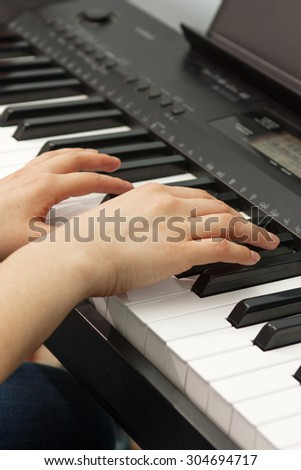 Hands of the musician on the piano keys