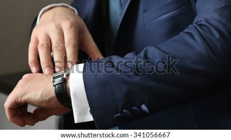 Hands of wedding groom getting ready in suit, selective focus