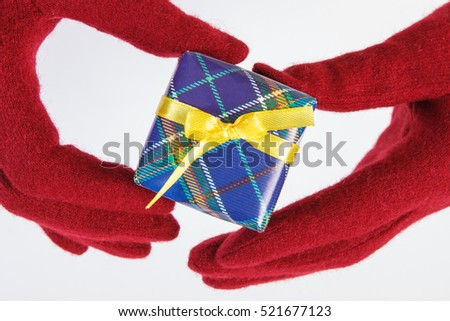 Hands of woman in red woolen gloves with wrapped colorful gift for Christmas, Valentine, birthday or other celebration, white background