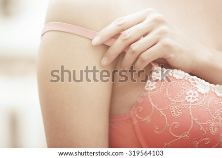 Hands of woman undressing pink bra
