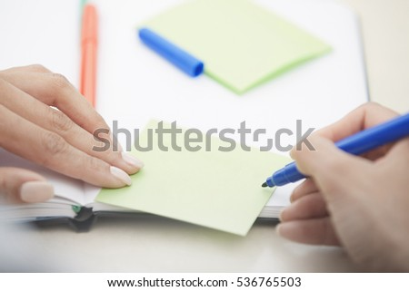 Hands of woman writing on adhesive note with empty space