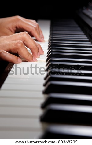 Hands playing on the digital hybrid piano, taken with spotlighting