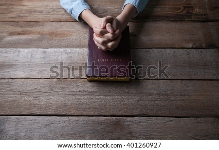 hands praying with a bible in a dark over wooden table