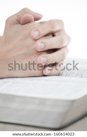hands praying with bible on table