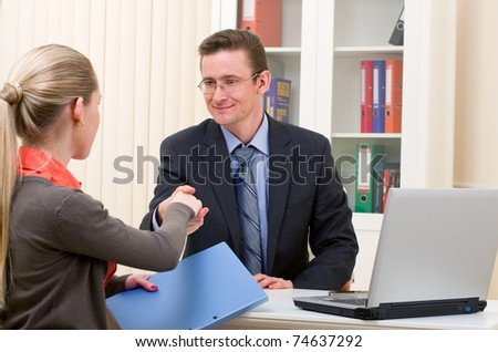 hands shake between two successful business people: man and woman at office place