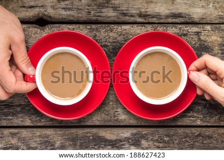 Hands taking cup of coffee on wood background