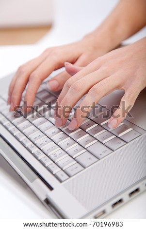 Hands typing on the keyboard of a laptop computer