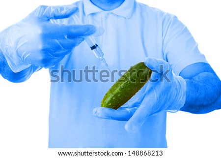 Hands with disposable gloves making injection with syringe to green cucumber. Biotechnology concept