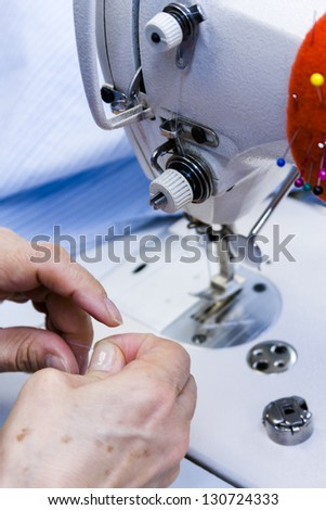 Hands work a sewing machine.