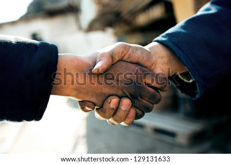 handshake of two workers at a factory close up