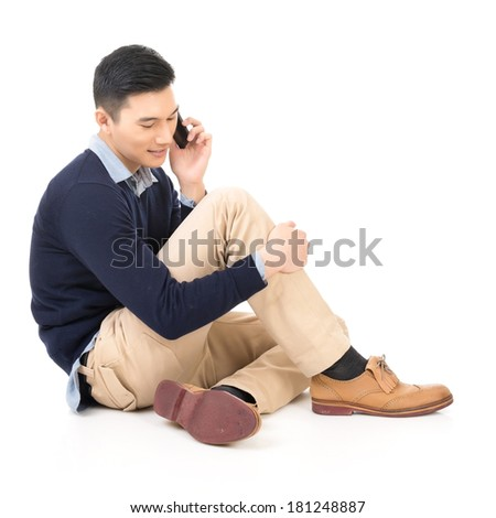 Handsome Asian guy sit and take a call, full length portrait isolated ...