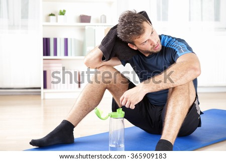 Handsome Athletic Man Wiping his Head with Towel While Resting After his Indoor Exercise At Home, Looking to the Right of the Frame.