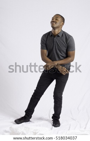 Handsome black man looking pleased, dancing for joy