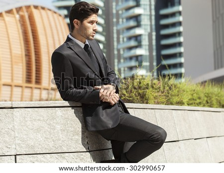 Handsome businessman and city background