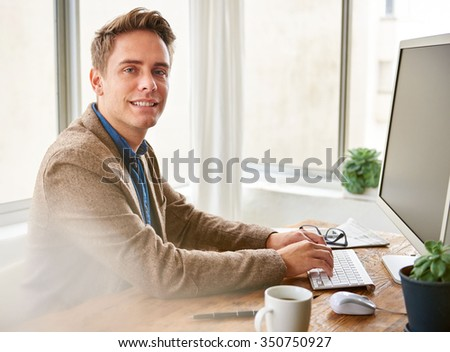 Handsome businessman looking positively at the camera while working at his desk
