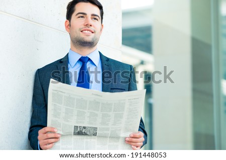Handsome businessman or manager, in front of modern office architecture, reading newspaper