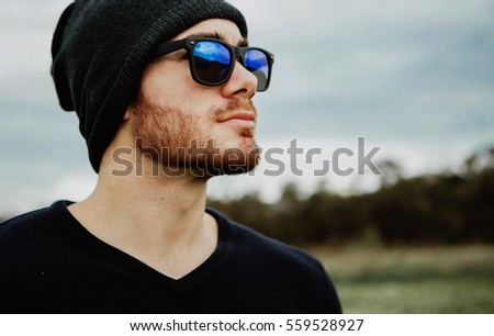 Handsome cool young man with sunglasses and cap wool
